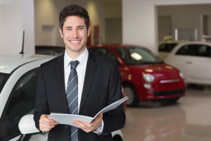 Businessman reading over a booklet smiling at camera at new car showroom